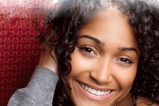 An attractive woman with dark curly hair and a perfect white smile thanks to her cosmetic dentist n New Jersey